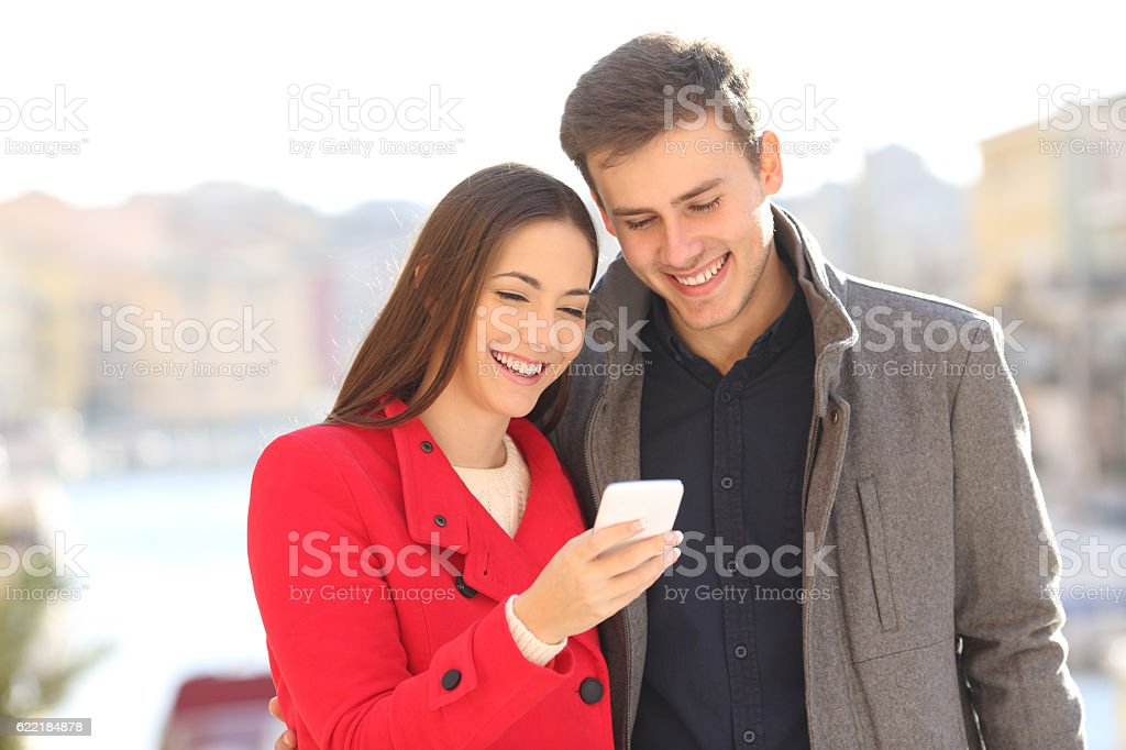 Couple sharing smart phone in winter stock photo