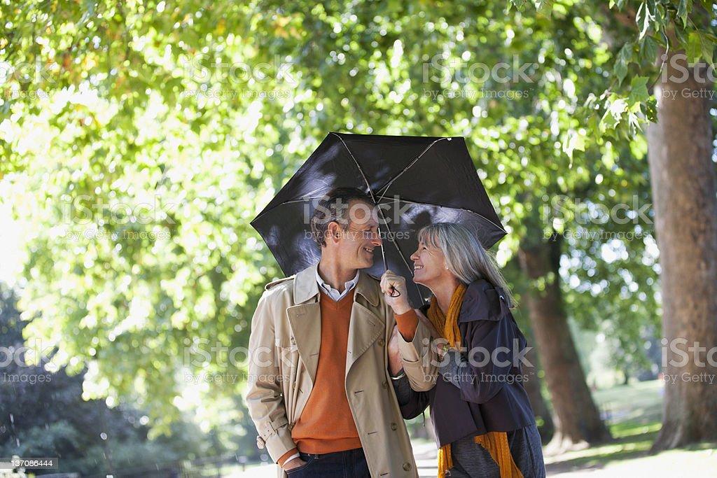 Couple sharing umbrella in sunny park royalty-free stock photo