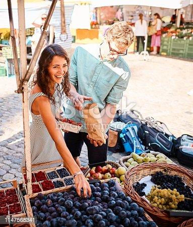 istock Couple shop at outdoor summer fruit market 1147568341