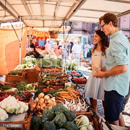 istock Couple shop at outdoor summer fruit market 1147569801