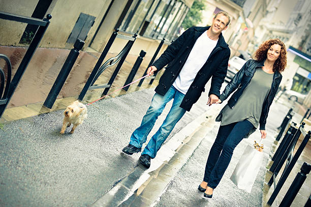 Couple shopping and walking under the rain stock photo