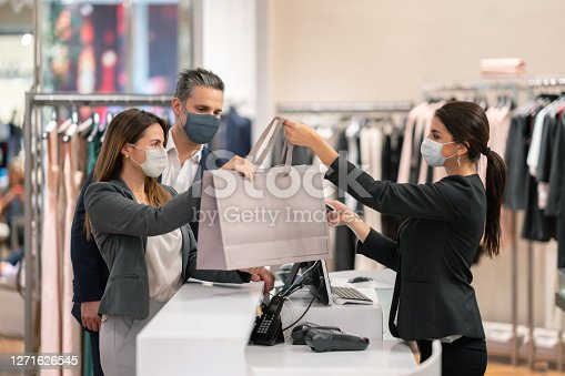 Latin American couple shopping at a clothing store and using facemasks during the pandemic while paying at the till