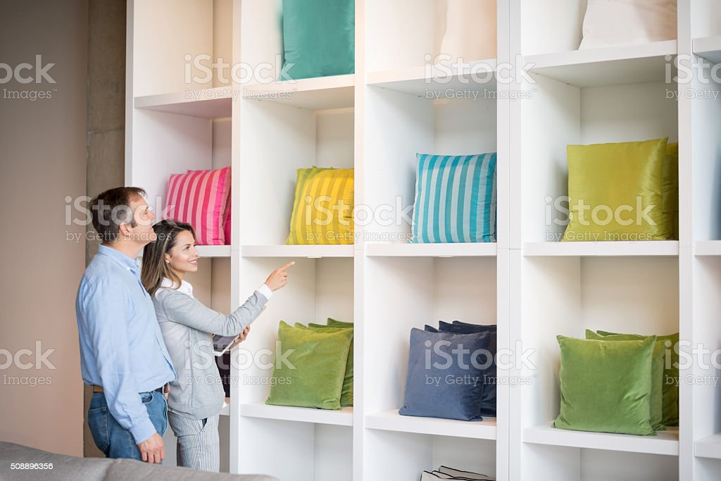 Loving couple shopping for cushions at a furniture store and looking...