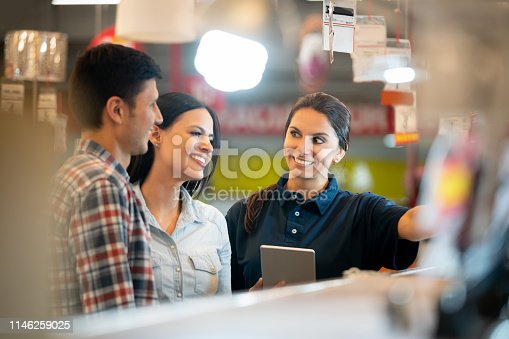 Portrait of a couple shopping at a home improvement store and talking to a saleswoman while smiling