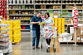 Happy couple shopping at a home improvement store following a list on a clipboard and smiling – business concepts