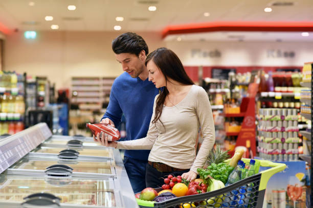 couple shopping for groceries at the supermarket stock photo