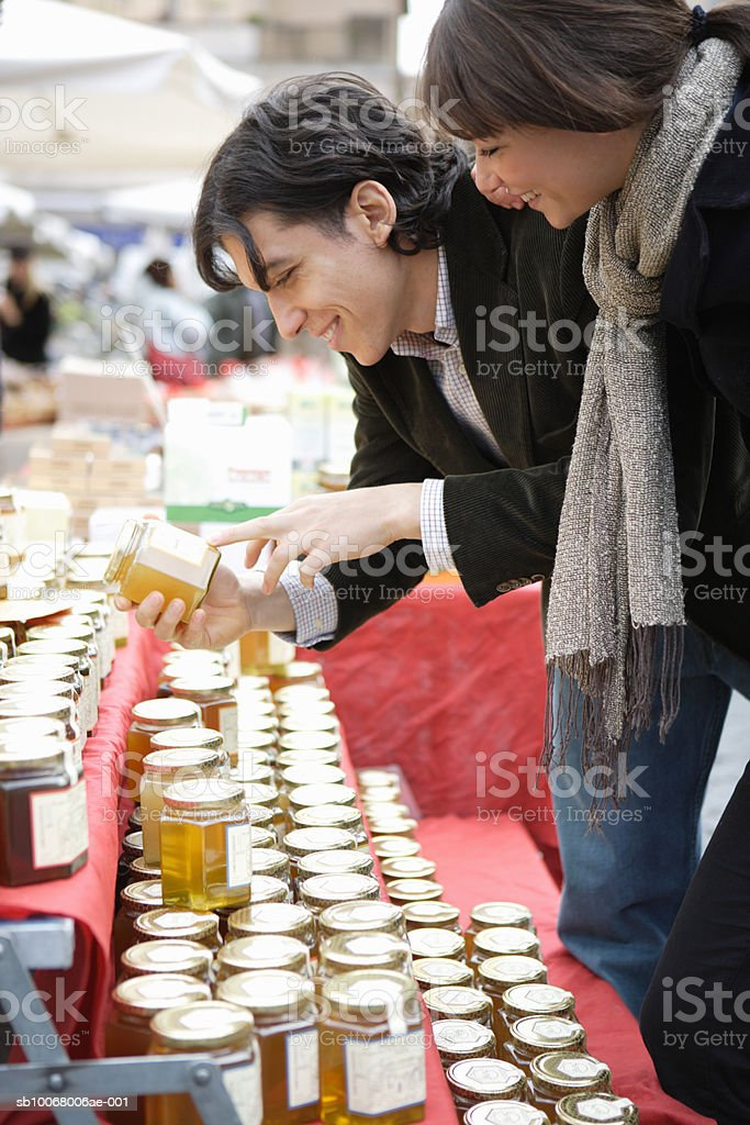 Couple shopping for honey at outdoor market royalty-free 스톡 사진