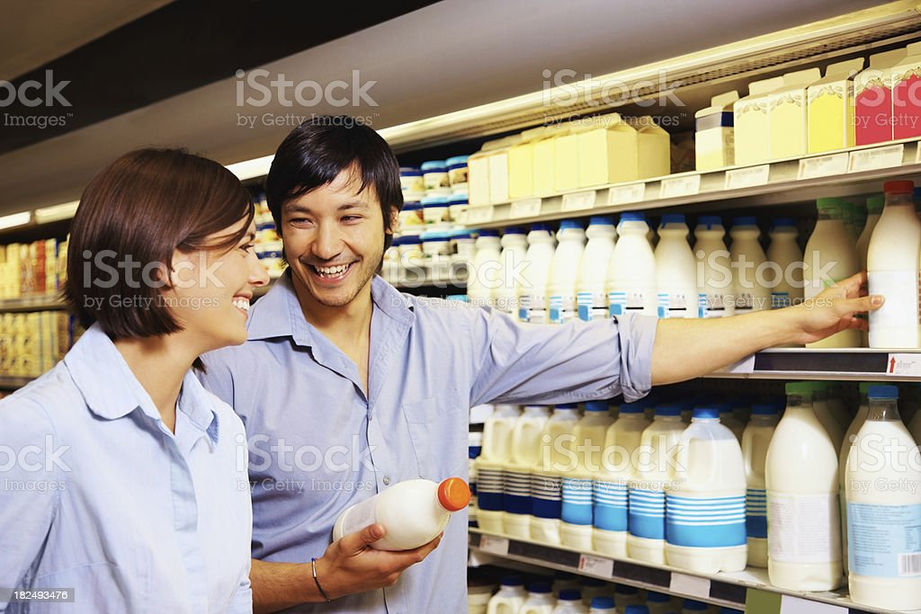 Couple shopping for milk at the supermarket royalty-free stock photo