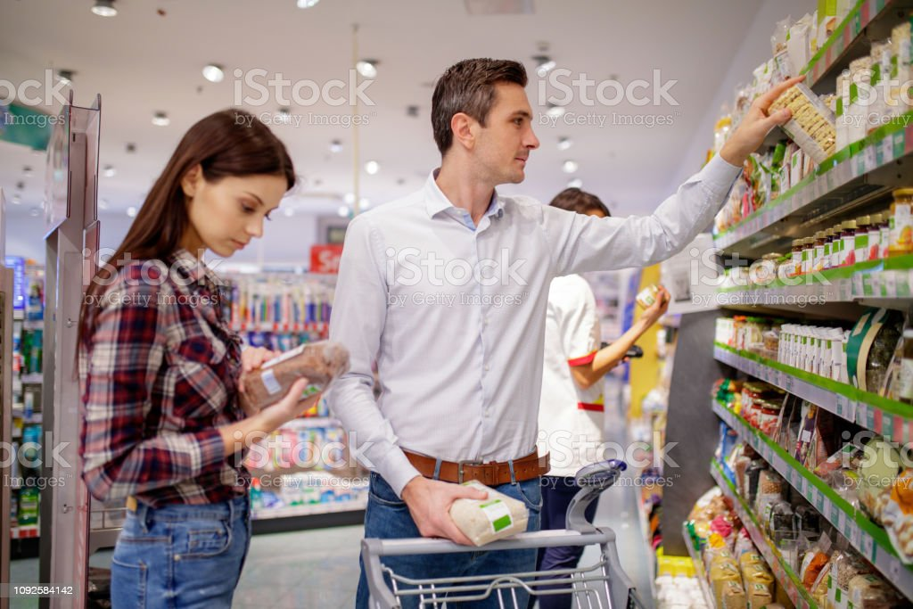 Couple Shopping For Organic Food In Supermarket Stock Photo