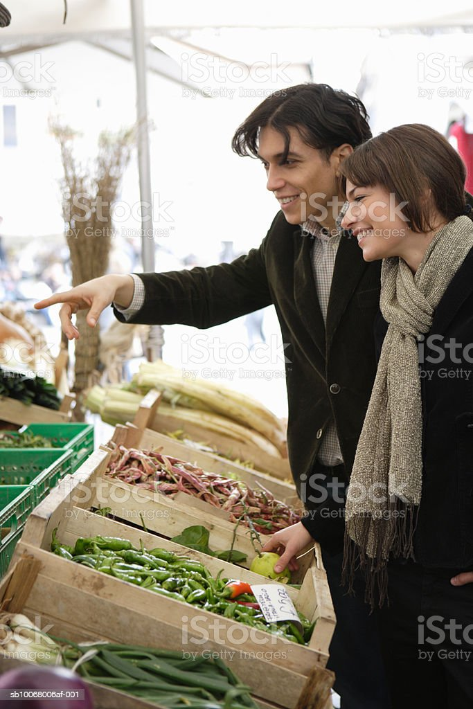 Couple shopping for vegetables at outdoor market royalty-free stock photo
