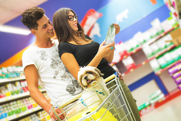 couple shopping in pet store with shih tzu in foreground - pet shop and dogs not cats stock pictures, royalty-free photos & images