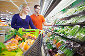 Couple shopping in produce section of supermarket