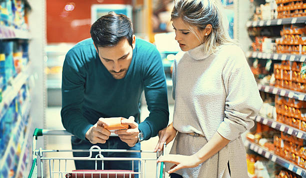 couple shopping in supermarket. - nutrition label stock photos and pictures