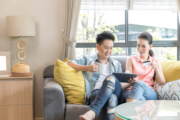 Couple shopping online at home Young Couples using tablet to shopping with credit card in living room of contemporary house for modern lifestyle and e-commerce concept shopping couple asian stock pictures, royalty-free photos & images