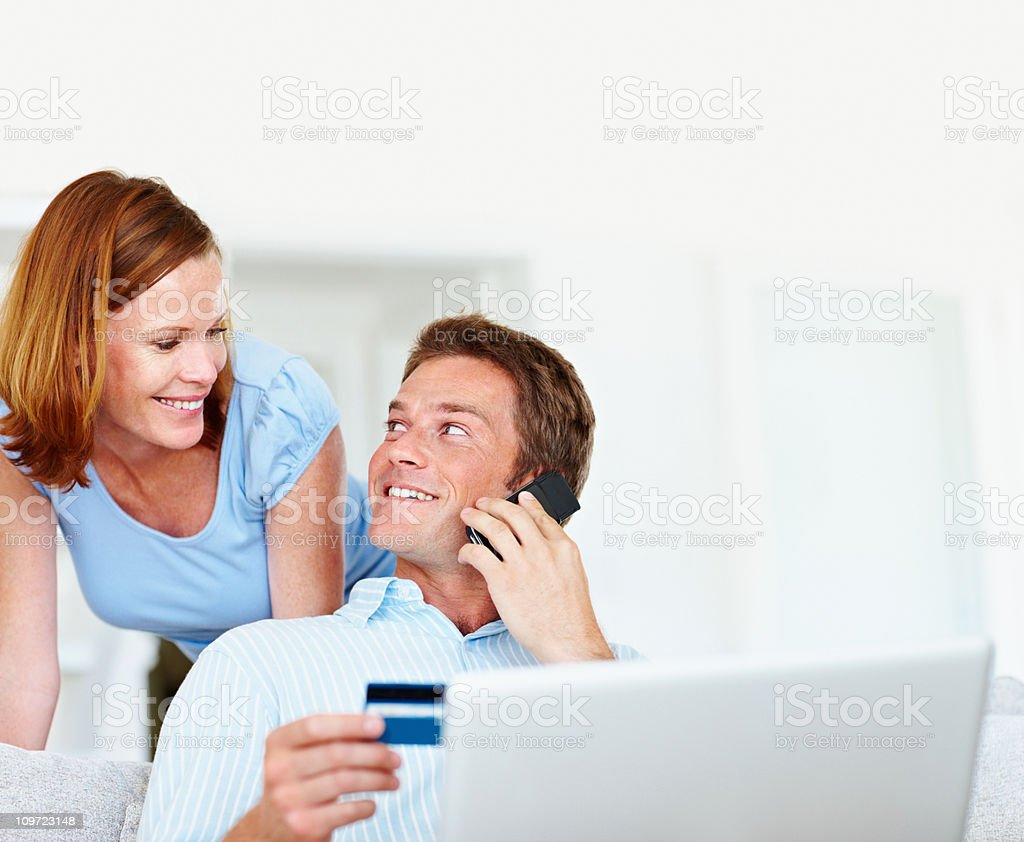 Couple shopping online while man using cellphone royalty-free stock photo