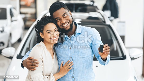 Black Family Couple Showing New Car Key Smiling To Camera In Dealership Showroom. Happy Spouses Hugging Near Their Auto. Panorama