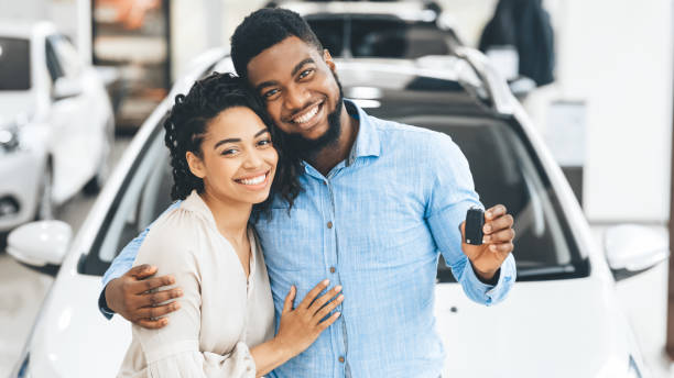 pareja que muestra nueva llave de coche sonriendo en el showroom del concesionario, panorama - comprar fotografías e imágenes de stock