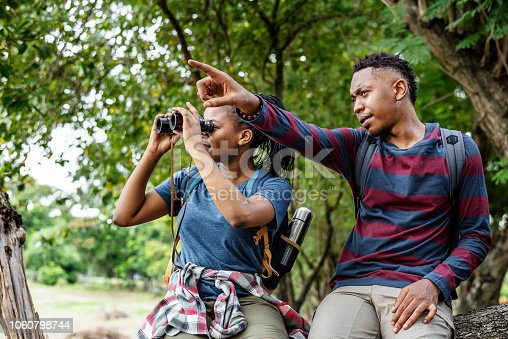 Couple sight seeing with binoculars in the forest