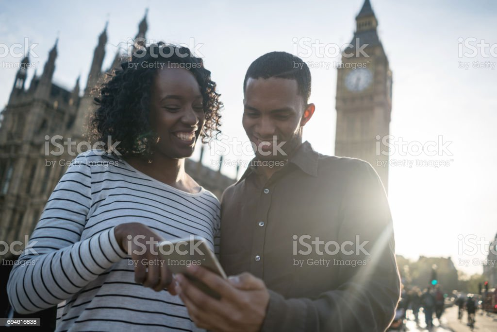 Couple sightseeing and using app on their cell phone stock photo