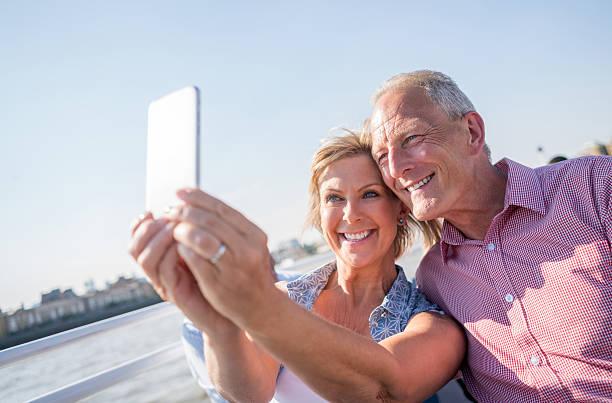 couple sightseeing taking a selfie on a boat - senior bilder wasser stock-fotos und bilder