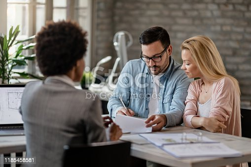 944314580 istock photo Couple signing a contract on a meeting with real estate agent. 1185458581
