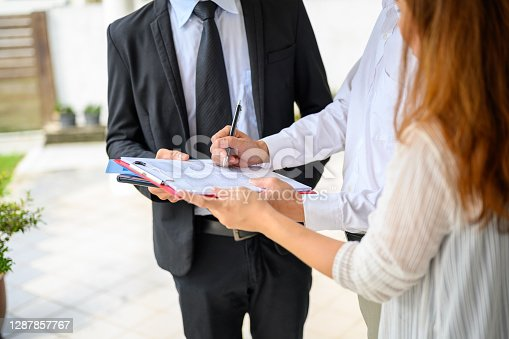 Couple signing contract agreement with digital tablet from real estate agent in front of their new house. Concept for real estate, moving home or renting property.