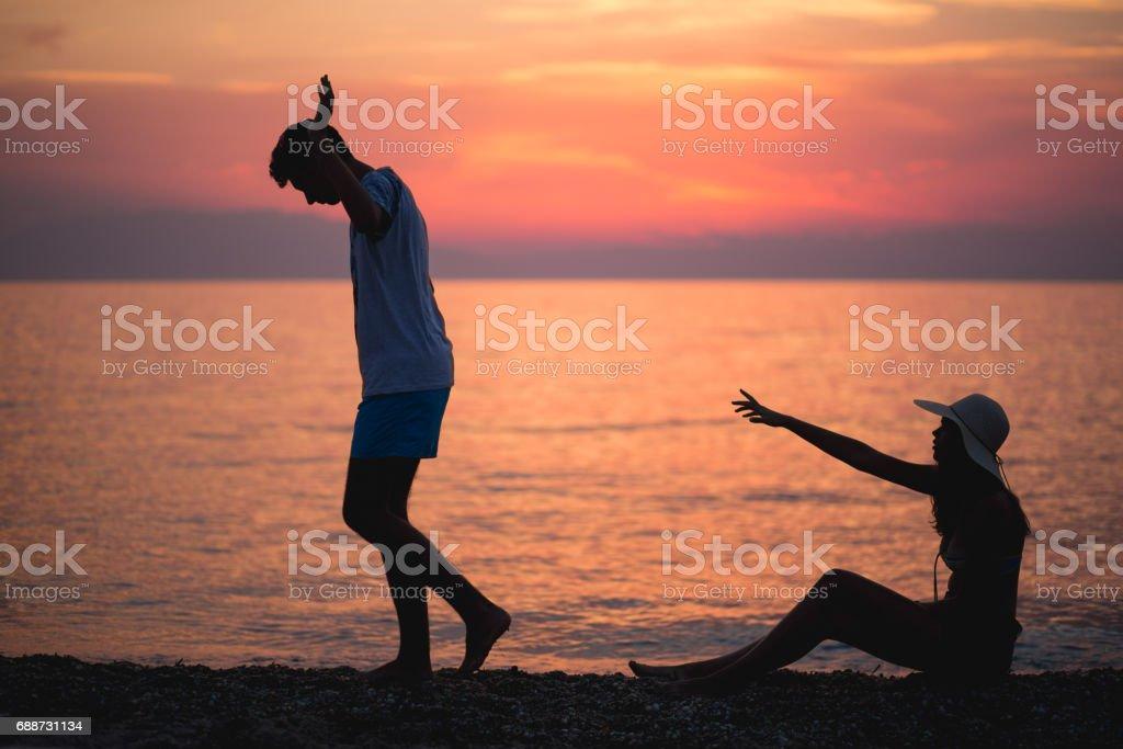 夕暮れ時のビーチで関係を壊すカップルのシルエット ストックフォト