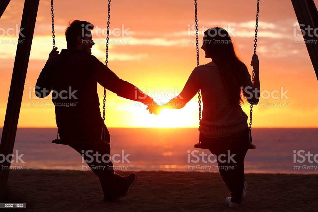 couple silhouette holding hands watching a sunrise royalty free stock photo