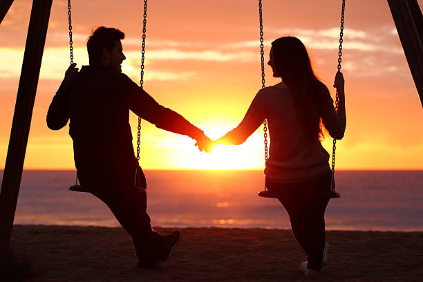 Couple silhouette holding hands watching a sunrise Back light portrait of a couple silhouette sitting on swing holding hands watching a sunrise on the beach with the sun in a warmth background love at first sight stock pictures, royalty-free photos & images