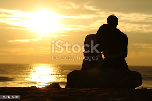 istock Couple silhouette watching sunset on the beach 492618942