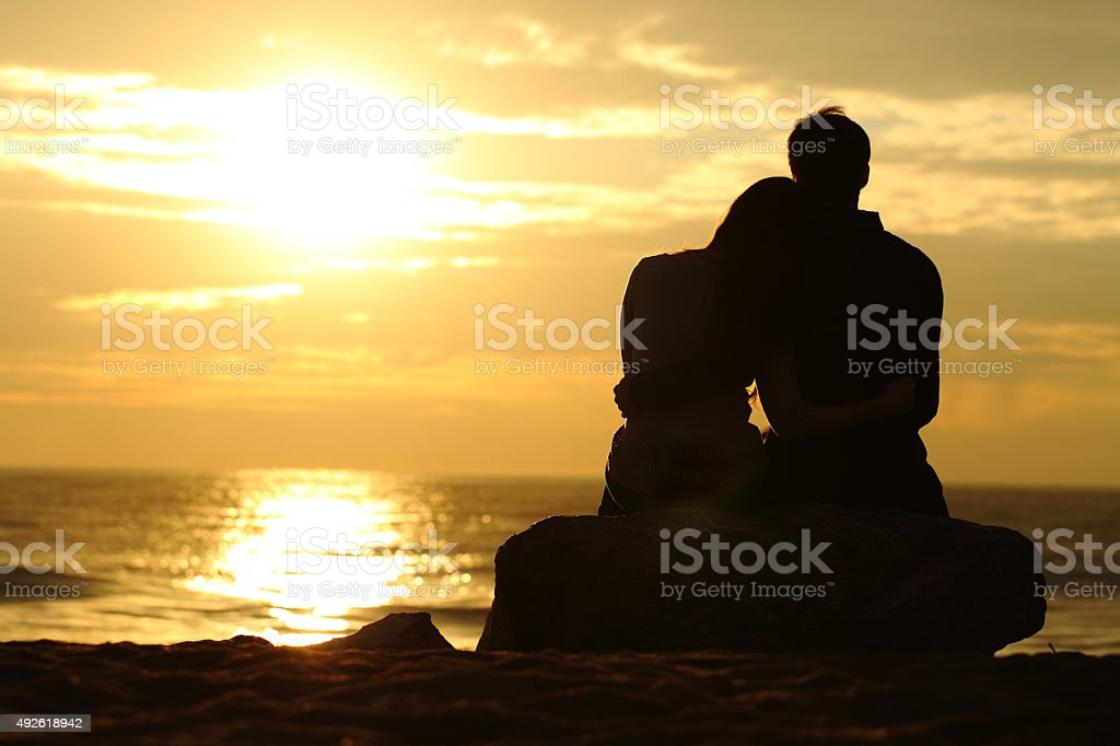 Couple silhouette watching sunset on the beach stock photo