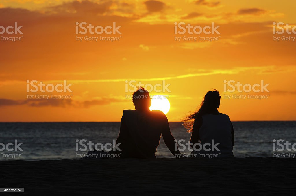 A couple silhouetted against a beach sunset, Maui, Hawaii stock photo
