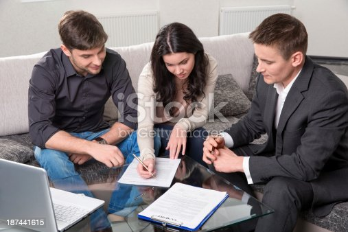 466848706 istock photo Couple singing documents with agent while sitting on couch 187441615