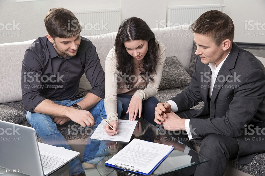 Couple singing documents with agent while sitting on couch stock photo