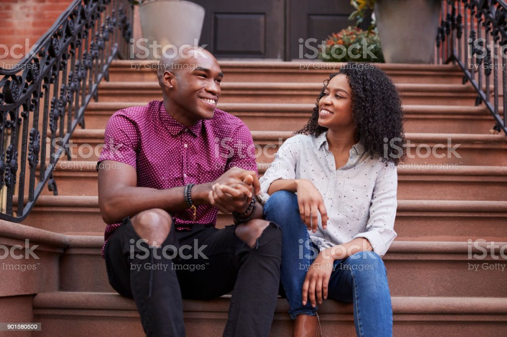 Couple Sit And Talk On Stoop Of Brownstone In New York City stock photo