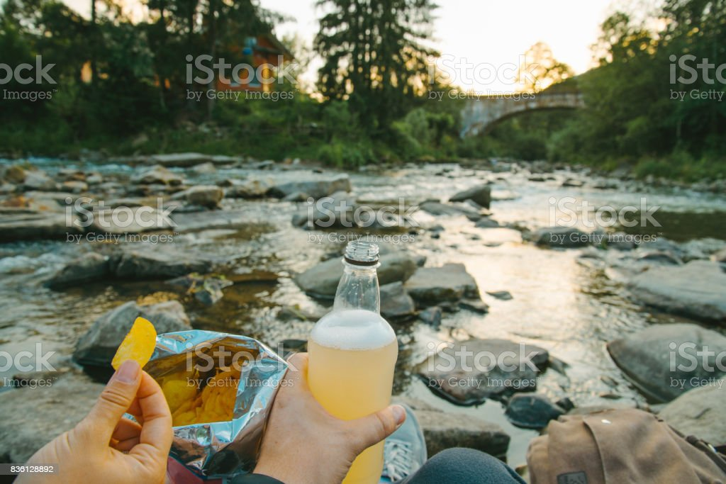 couple sit near mountain river with chips and beer stock photo