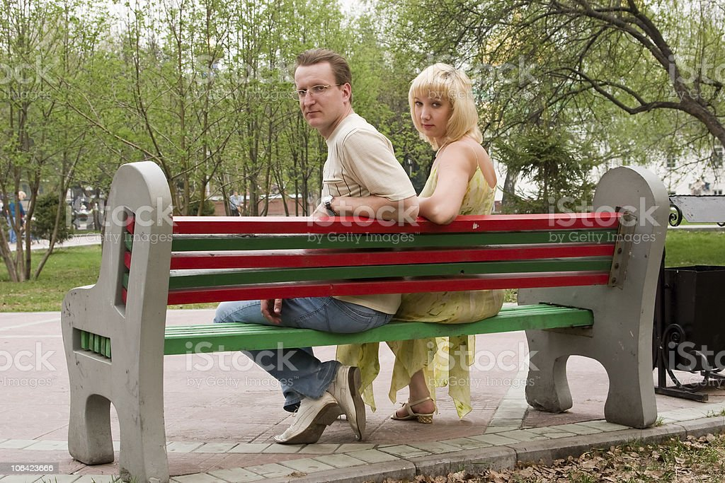 Couple sit on bench in park. stock photo