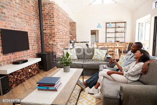 istock Couple Sit On Sofa In Open Plan Lounge Watching Television 672419728