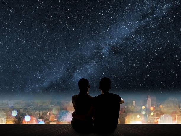 couple sit under strars stock photo