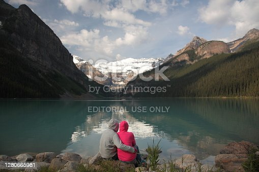 Couple siting on rock by the lake watching Mount Victoria with Victoria Glacier and Lake Louise during summer in Banff National Park, Canadian Rockies, Alberta, Canada.