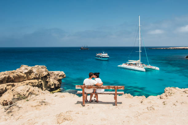 a couple sits on a bench and looks at the lagoon - cyprus стоковые фото и изображения