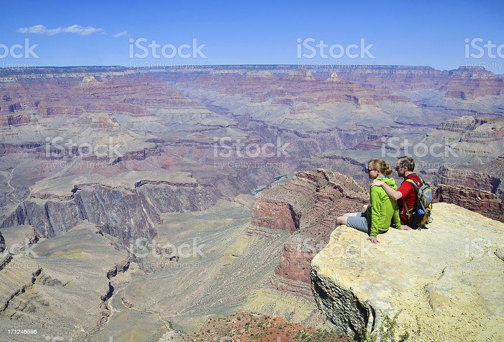 Couple sitting above Grand Canyon stock photo