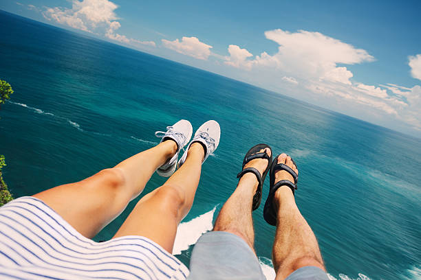 couple sitting above the ocean - woman leg beach pov stock photos and pictures