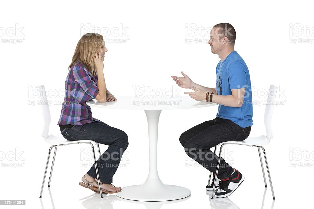 Couple sitting across from one another at a table stock photo