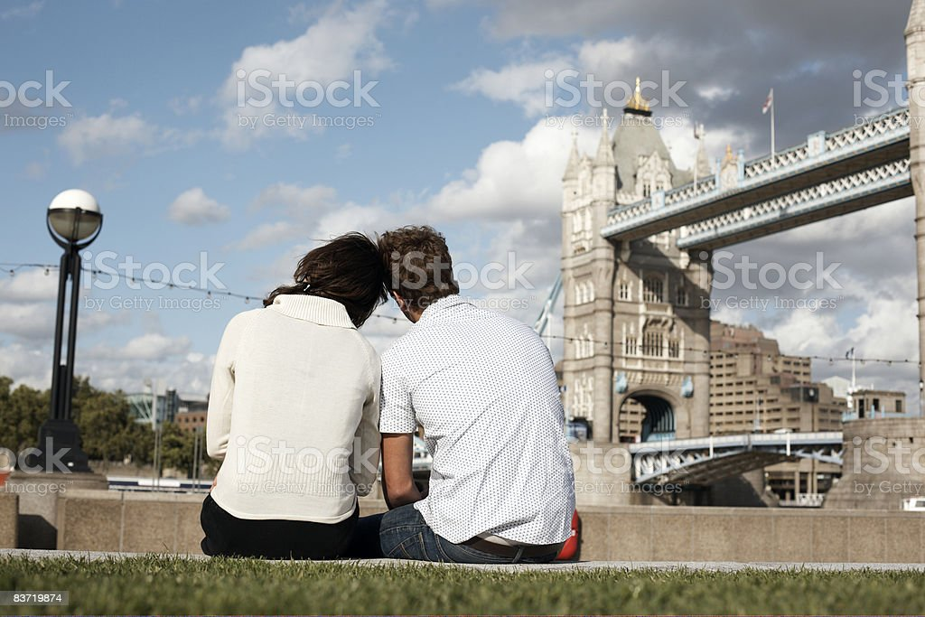 Couple sitting admiring Tower Bridge royalty free stockfoto