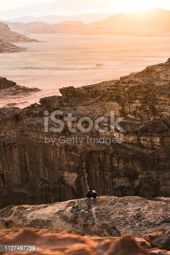 Couple sitting and looking at scenic view of Wadi Rum desert from rock