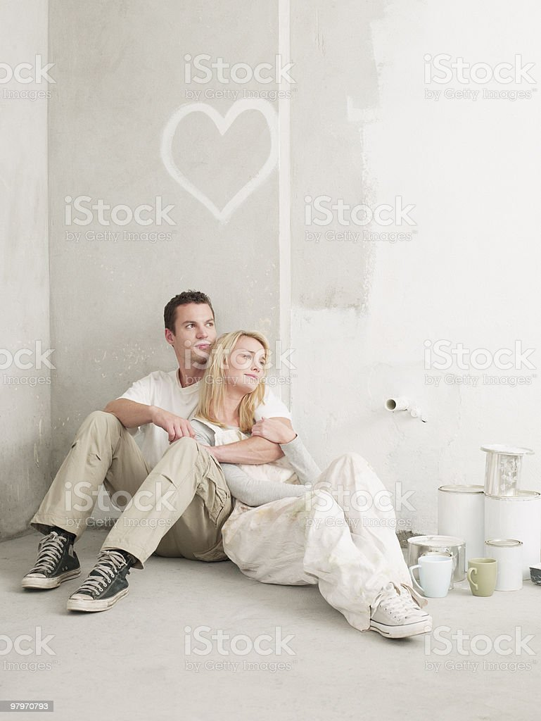 Couple sitting and relaxing under heart painted on wall royalty-free stock photo
