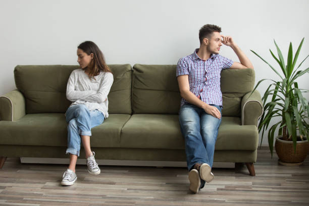 Couple sitting apart not talking because of quarrel stock photo