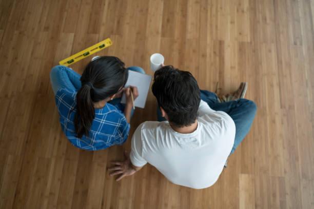 paar, sitzen an einem leeren raum reden, innenarchitektur - umzug checkliste stock-fotos und bilder
