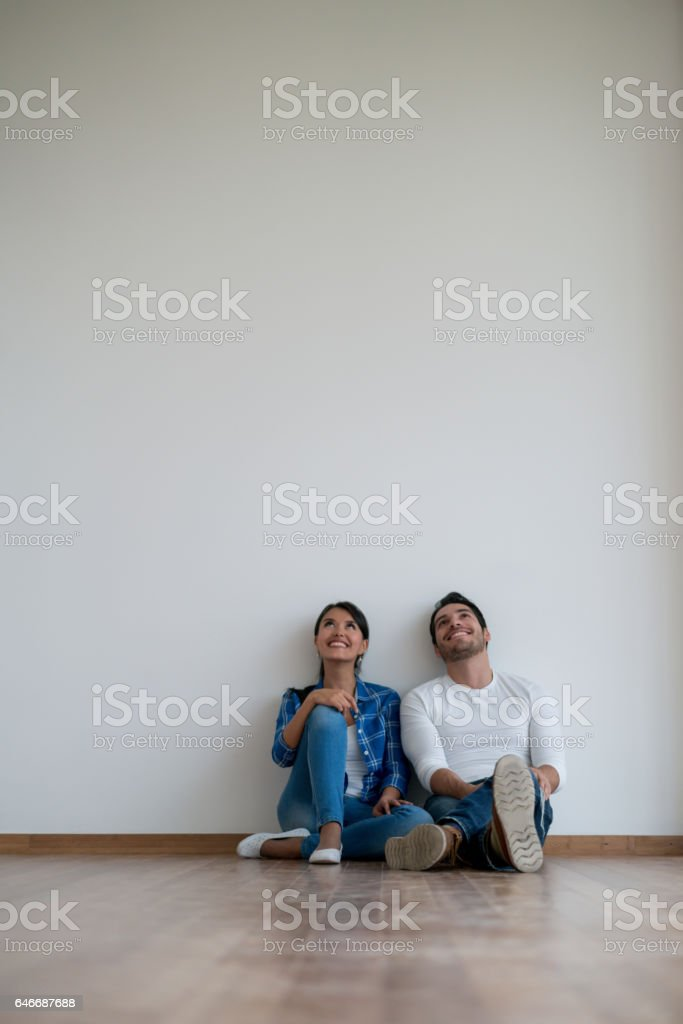 Couple sitting at an empty room talking about interior design stock photo